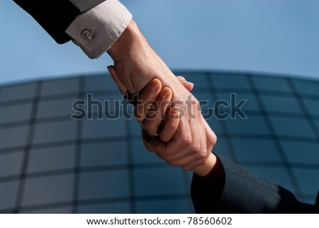 Handshake unrecognizable business man and woman on modern building background - stock photo