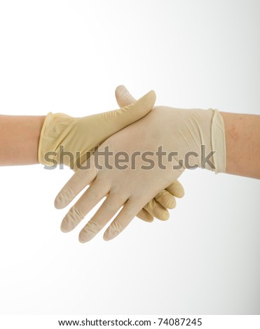 Handshake with hands wearing latex protective gloves - stock photo