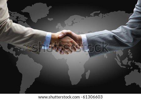 Handshake with map of the world in background - stock photo
