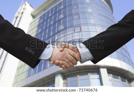 Handshake with modern skyscrapers as background - stock photo