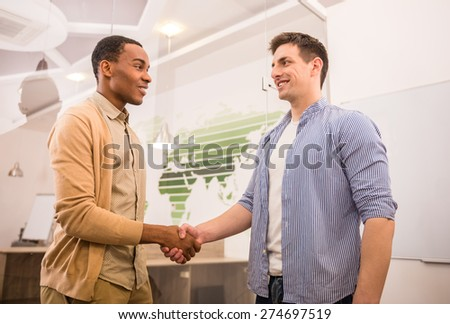 Handshakes of two international business men in casual clothes. - stock photo