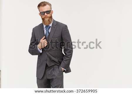 Handsom beard male model in suit and sunglasses against white background - stock photo