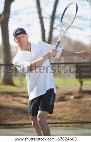 Handsome active sports man tennis player outside