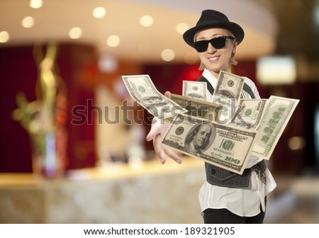 Handsome adult business woman in cap throwing dolla - stock photo