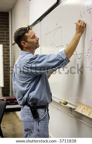 Handsome adult education teacher writing math problems on the board.  Vertical View - stock photo