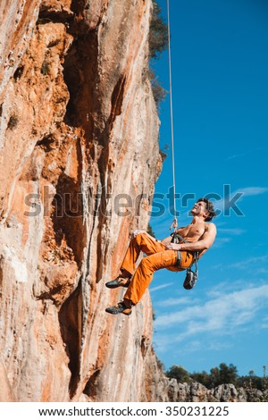 Handsome adult male rock climber hanging on belay rope over the blue sky and mountains. Stock Image