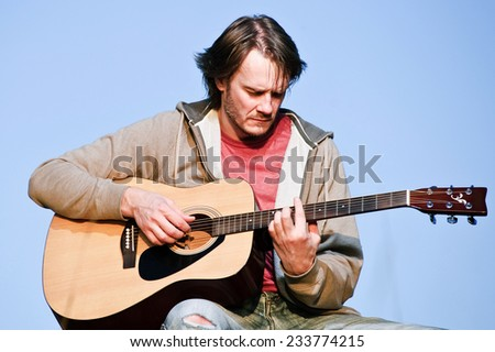 Handsome adult man with guitar outdoors. - stock photo