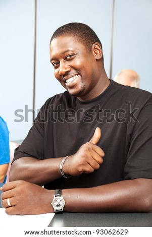 Handsome african-american adult college student gives thumbs up. - stock photo