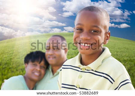 Handsome African American Boy with Proud Parents Standing Over Clouds, Sky and Arched Horizon of Grass Field. - stock photo