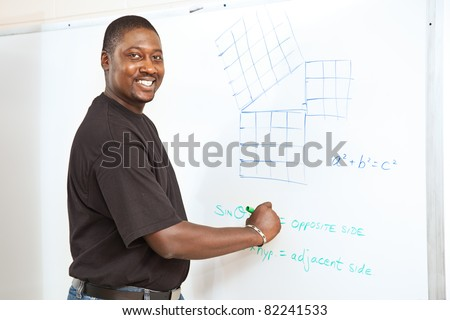 Handsome African-American college student (or teacher) doing trigonometry equations on the white board. - stock photo