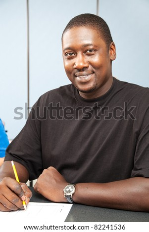 Handsome african-american college student sitting in class. - stock photo