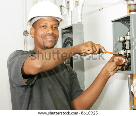 Handsome african american electrician working on a breaker panel.  Model is an actual electrician performing work according to industry safety and code standards. - stock photo