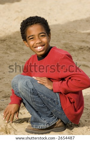 Handsome African American kid sitting outside at the beach