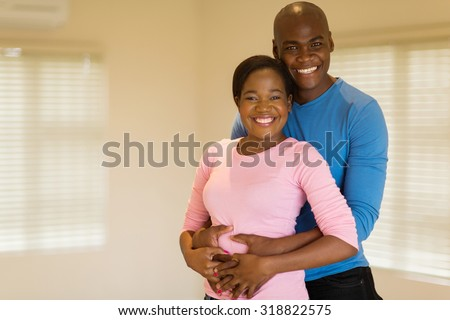 handsome african american man hugging his pretty girlfriend - stock photo