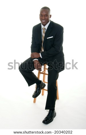 Handsome African American man in a black business suit casually sitting on a stool. - stock photo
