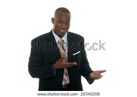 Handsome African American man in a black business suit gesturing as if to demonstrate a product sample. - stock photo