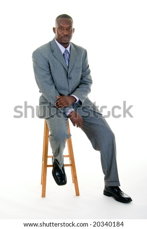 Handsome African American man in a gray business suit sitting on a stool. - stock photo