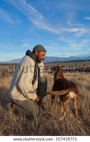Handsome African American man playing with his dog outdoors - stock photo