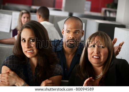 Handsome African-American man stands behind uncomfortable woman employees - stock photo