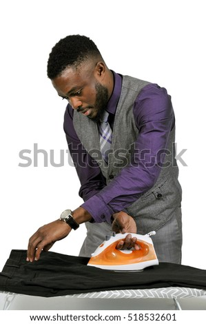 Handsome african american man with a clothes iron about to press his clothing