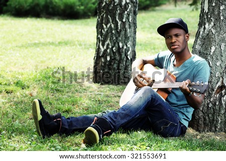 Handsome African American man with guitar sitting in park - stock photo
