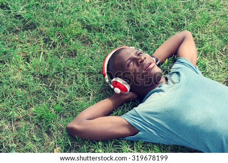 Handsome African American man with headphones lying on green grass - stock photo