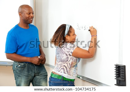 Handsome african-american math teacher works with a student at the board. - stock photo