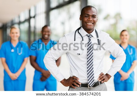 handsome african american medical doctor with colleagues in background - stock photo