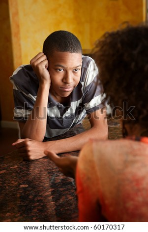 handsome African-American teen talks with woman in kitchen - stock photo