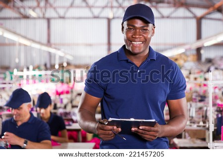 handsome african american textile worker holding a clipboard - stock photo