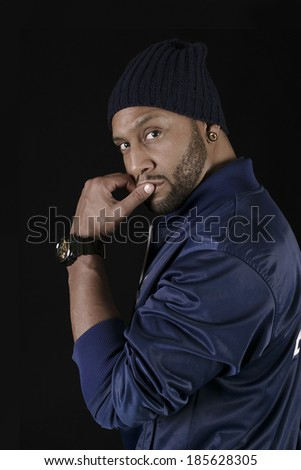 Handsome African American young man with a knit hat dressed in blue . Copy space - stock photo