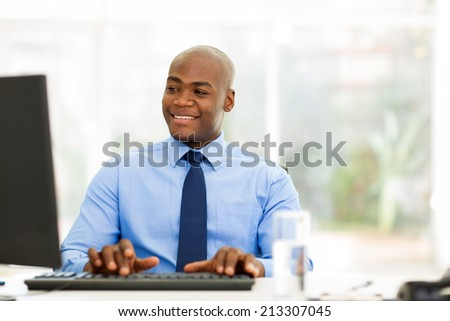 handsome african businessman looking at computer screen - stock photo