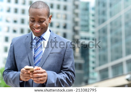 Handsome african businessman reading email on smart phone - stock photo