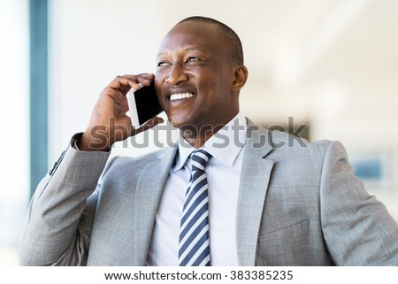 handsome african businessman talking on cell phone - stock photo