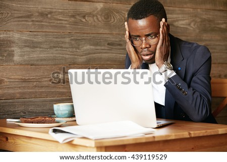 Handsome African corporate worker in glasses using laptop for distant work, sitting at the hotel lobby, looking at the camera in shock, surprised with sensational news, holding hands on his cheeks - stock photo