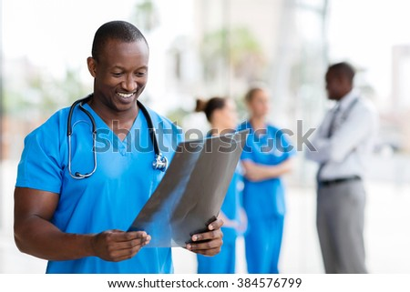 handsome african healthcare worker with x-ray - stock photo