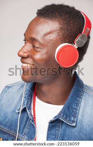 Handsome African man listening to music on DJ headphones - stock photo