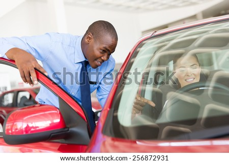 handsome african salesman explaining car features to potential customer - stock photo