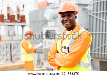 handsome african technician with colleague on background in substation - stock photo