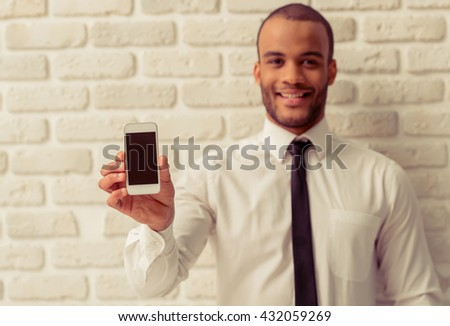 Handsome Afro American businessman in classic clothes is showing smartphone, looking at camera and smiling, against white brick wall. Phone in focus - stock photo
