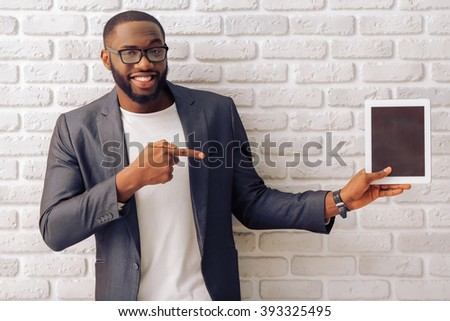 Handsome Afro American businessman in gray classic jacket and glasses is presenting a tablet and smiling, standing against brick wall - stock photo