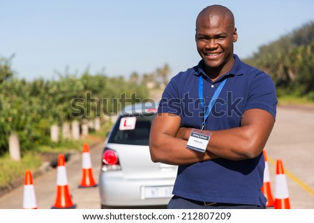 handsome afro american driving instructor with arms crossed - stock photo