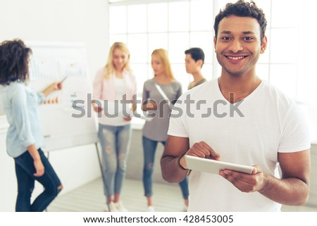 Handsome Afro American guy with tablet is looking at camera and smiling, in the background his colleagues are discussing business affairs - stock photo
