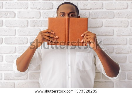 Handsome Afro American man in classic shirt is covering half face with a notebook, standing against white brick wall - stock photo