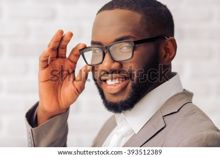 Handsome Afro American man in classic suit and glasses is looking at camera and smiling, against white brick wall, close up - stock photo