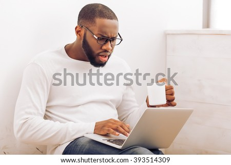 Handsome Afro American man in glasses is using a laptop and holding a cup while working at home