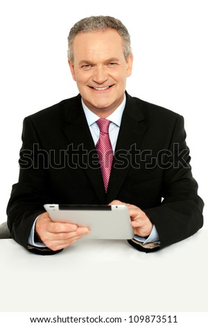 Handsome aged business male using tablet pc, smiling at camera - stock photo