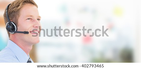 Handsome agent with headset against view of business stuffs on scale - stock photo