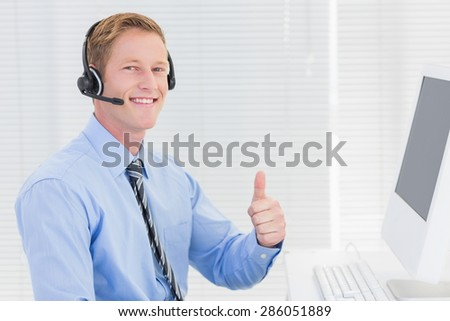 Handsome agent with headset smiling at camera in call center - stock photo