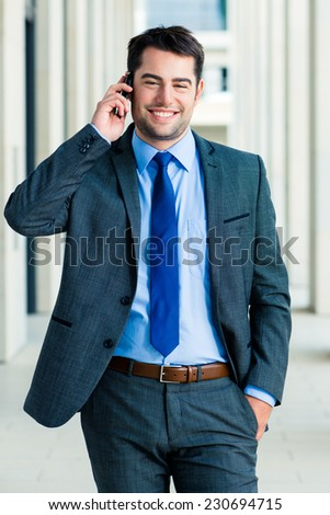 Handsome and confident businessman or manager talking on his business cell phone walking in front of modern architecture - stock photo